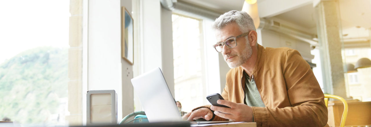 older man looking at a laptop and mobile phone